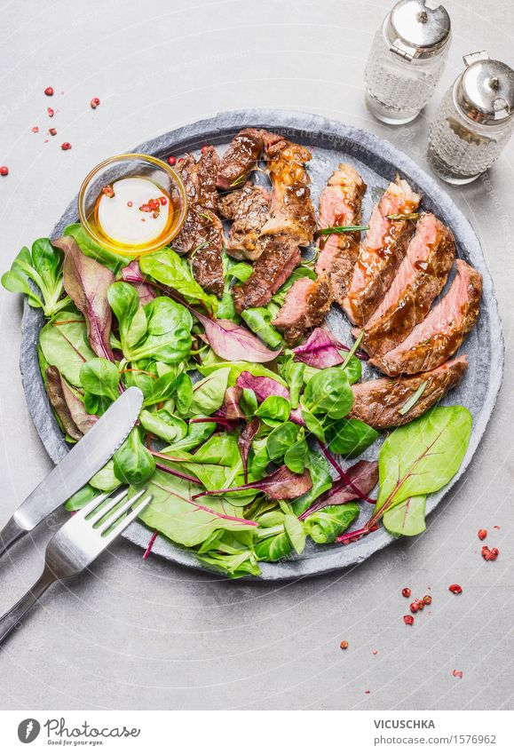 Sliced medium grilled steak and green salad Food Meat Lettuce Salad Herbs and spices Cooking oil Lunch Dinner Buffet Brunch Banquet Organic produce Plate