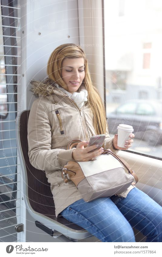 Blond woman sitting on commuter train Human being Woman Youth (Young adults) Beautiful Winter 18 - 30 years Adults Lifestyle Happy Think Hair Transport Blonde Sit Railroad Telephone