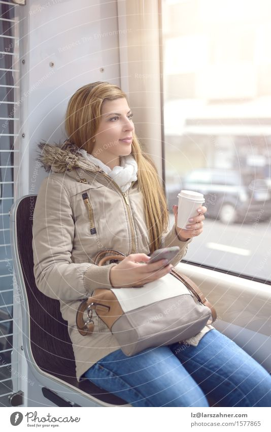 Blond woman sitting on commuter train Coffee Lifestyle Happy Beautiful Winter Telephone Woman Adults 1 Human being 18 - 30 years Youth (Young adults) Transport