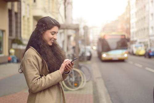 Brunette woman texting on her mobile phone Human being Woman Youth (Young adults) City Beautiful 18 - 30 years Face Adults Street Happy Business Transport