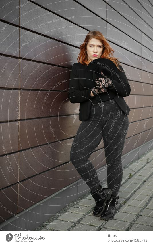 . Feminine 1 Human being Wall (barrier) Wall (building) Sidewalk Pants Jacket Boots Hat Red-haired Long-haired Observe Looking Stand Wait Beautiful Under