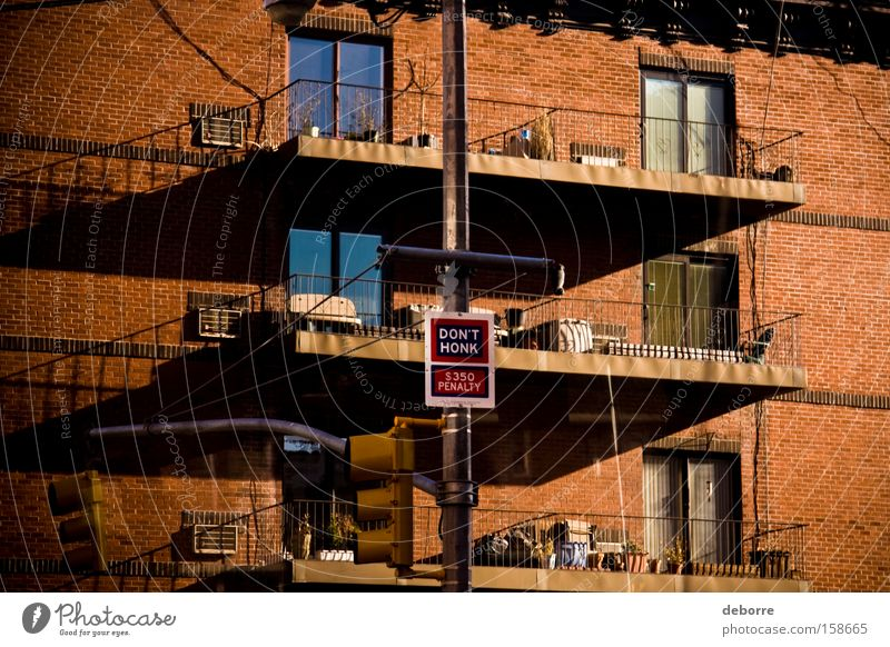 """""""Don't honk"""" penalty sign on a lamp post outside a New York red brick apartment building with balconies. Flat (apartment) House (Residential Structure) Window"""