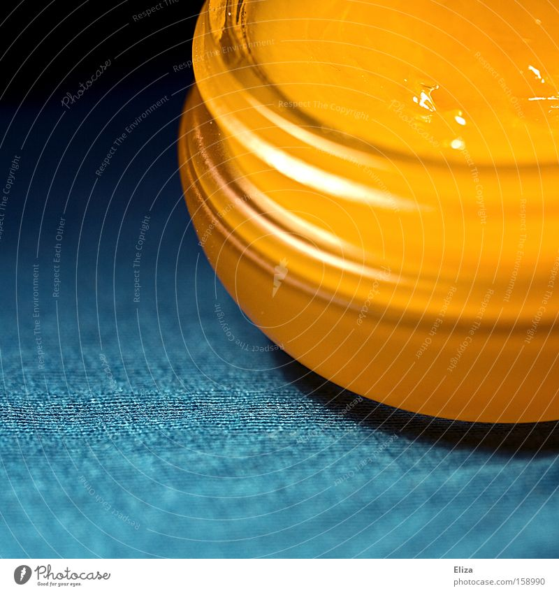 Close-up of a cream jar with an orange cream inside Gold Tin Plastic container turquoise Glittering Screw thread already Esthetic Macro (Extreme close-up)