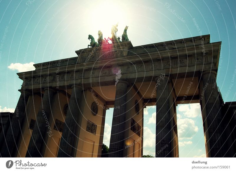 Brandenburg Gate against the light with blue sky Berlin Capital city Sun Summer Blooming Light Rider Carriage Horse Statue Monument Monumental Landmark Warmth
