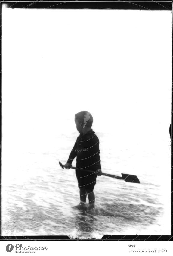 framework plot Child Black & white photo Historic Ocean Beach Playing Shovel Memory Souvenir Human being Vacation & Travel Offspring Boy (child) glass negative