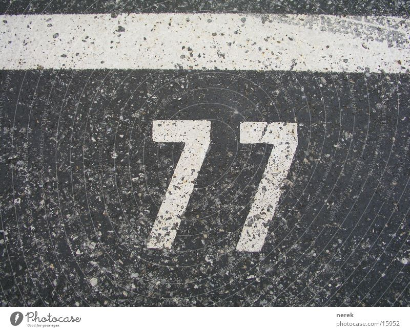 77 - holy number Digits and numbers Tar Parking lot Asphalt Skid marks Line Tracks Christianity Transport Street wise Signs and labeling