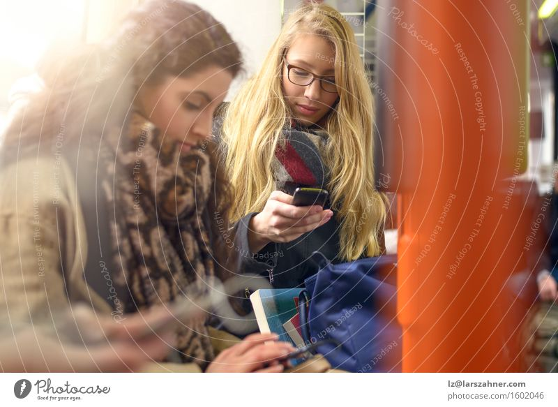 Two young women sitting on commuter train Reading Telephone PDA Technology Woman Adults Friendship 2 Human being 18 - 30 years Youth (Young adults) Scarf