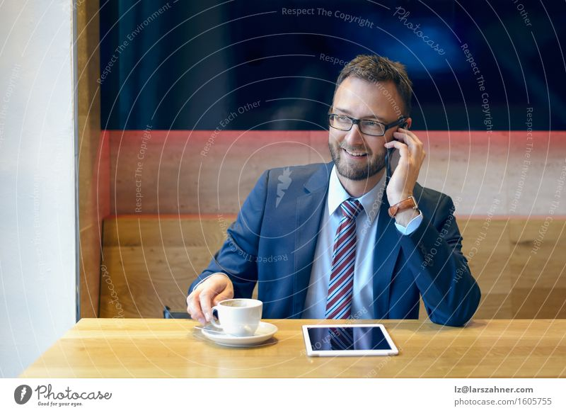 Handsome businessman in suit using a mobile phone Coffee Work and employment Business Telephone Technology Man Adults Suit Tie Eyeglasses Beard Going Smiling