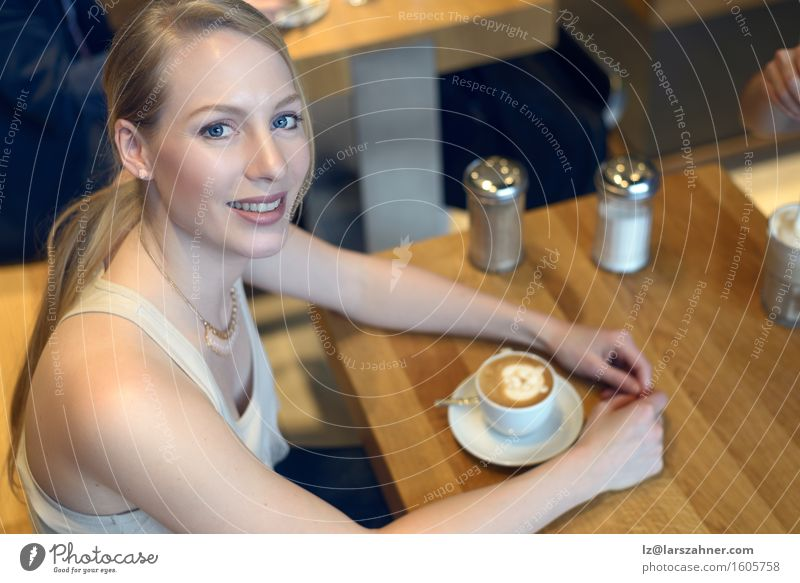 Smiling blond woman sitting in a bar with a cappuccino Coffee Lifestyle Beautiful Relaxation Table Feminine Woman Adults 1 Human being 18 - 30 years