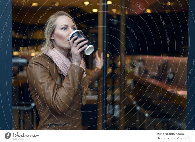 Blond woman sipping coffee from a cup while leaving a bistro Human being Woman Youth (Young adults) Winter 18 - 30 years Adults Feminine Going Copy Space Blonde
