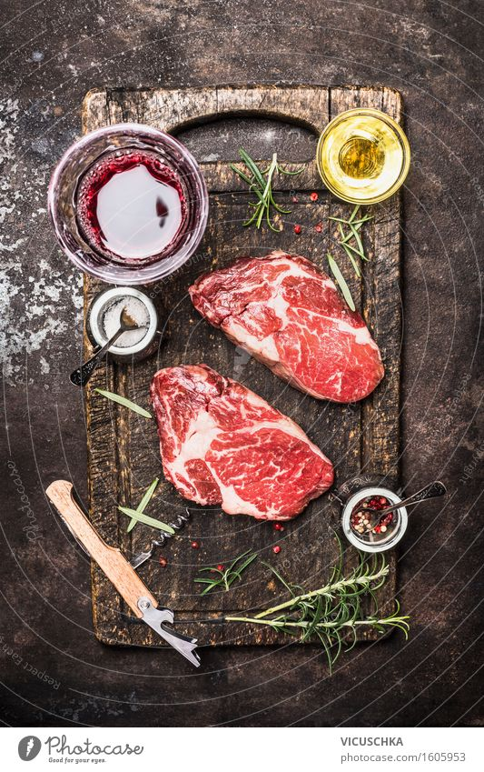 Two raw beef steaks with glass of wine, herbs, oil and spices. Meat Herbs and spices Cooking oil Nutrition Lunch Dinner Buffet Brunch Banquet Organic produce