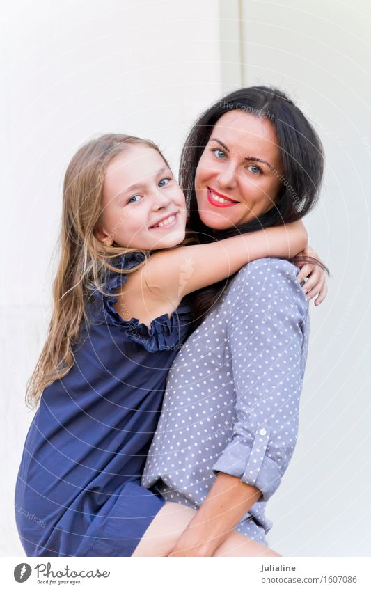 Embracing brunette mother and blond daughter Child Schoolchild Girl Woman Adults Parents Mother Infancy 2 Human being 3 - 8 years 8 - 13 years 18 - 30 years