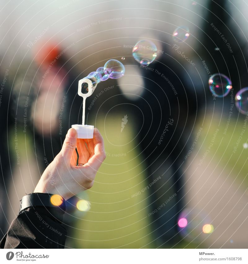 soap bubbles Human being Hand Group Kitsch Small Soap bubble Multicoloured Flying Dream Wind Playing Air bubble Colour photo Subdued colour Exterior shot