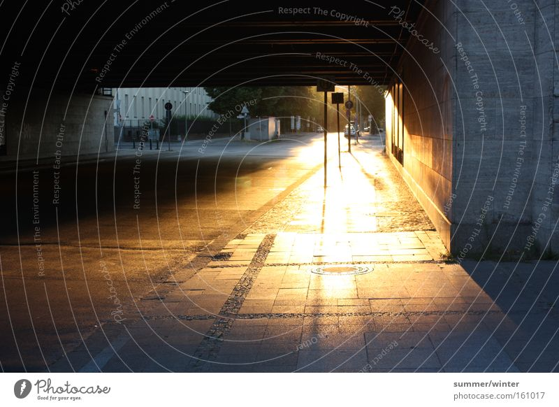glowing footpath Sunset Dusk Underpass Bridge Berlin Town Nature Summer Warmth Sidewalk Street Cobblestones Street sign Stop (public transport) Orange Flashy
