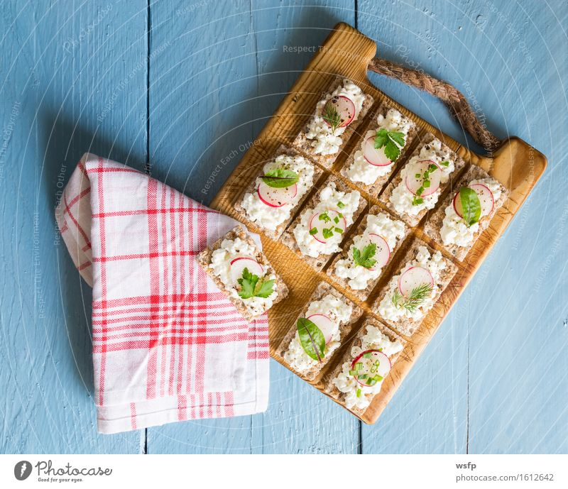 Crispbread with cottage cheese radishes and herbs Herbs and spices Wood Blue Radish Cream cheese Chives Dill Parsley beetroot leaves Wooden board Snack
