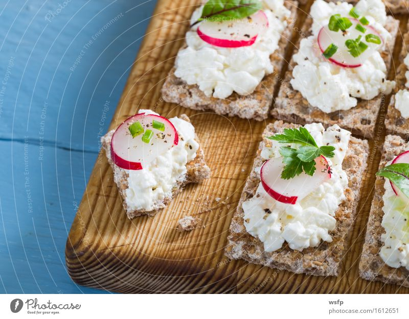 Crispbread with cottage cheese radishes and herbs Herbs and spices Wood Blue Cream cheese Radish Chives Dill Parsley beetroot leaves Wooden board Snack