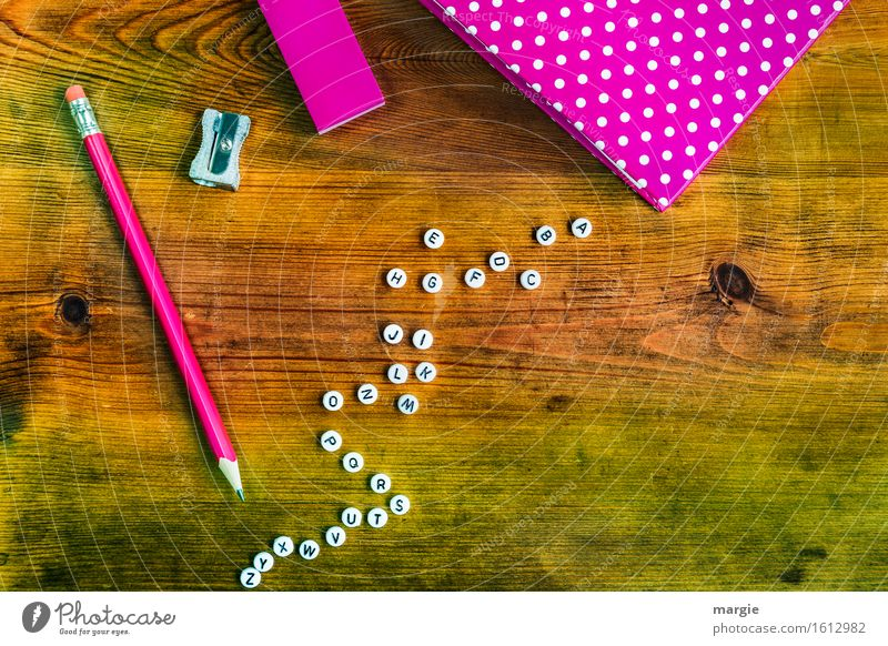 All letters of the alphabet, a notebook, a pencil and an eraser in pink on a wooden table School Study Work and employment Profession Office work Workplace