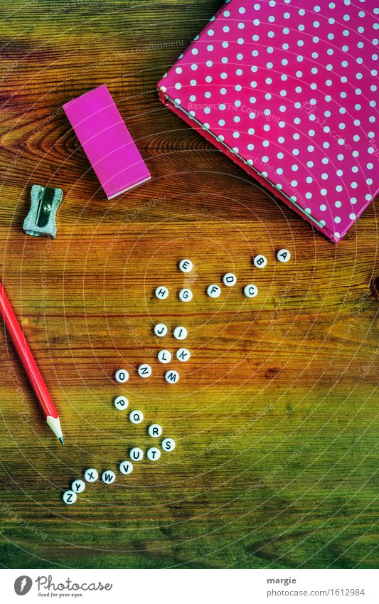 Alphabet with white letters, a notebook and eraser in pink, a red pencil and a sharpener on a wooden table Leisure and hobbies Education School Study