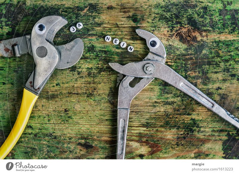 The letters NO and YES and two tongs with eyes on an old wooden table Profession Craftsperson Workplace Construction site Services Craft (trade) To talk Team