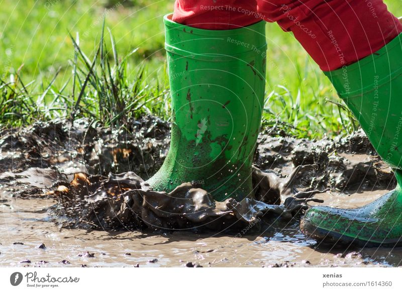 Green rubber boots splashing in muddy puddle Rubber boots Puddle Mud slush Playing Child Feet Human being Water Drops of water Meadow Jump Dirty Wet Brown Red
