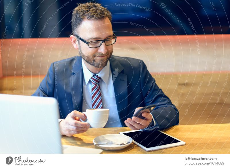 Businessman enjoying his coffee Coffee Face Work and employment Telephone Computer Notebook Technology Man Adults 1 Human being 30 - 45 years Suit Eyeglasses