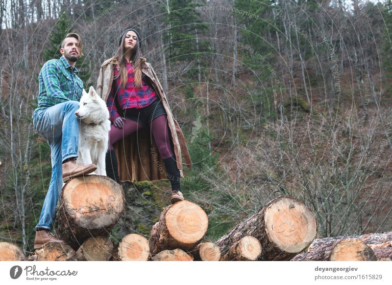 Young woman and men on wood logs in the forest Lifestyle Happy Leisure and hobbies Girl Woman Adults Man Couple Nature Tree Park Forest Fashion Footwear Dog