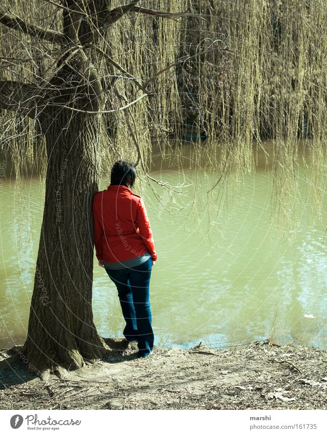 Lost in thought Lake Tree Brook Longing Loneliness Far-off places Thought Dreamily Red Green Gloomy Sadness Emotions Woman Jacket Grief Distress River Spring