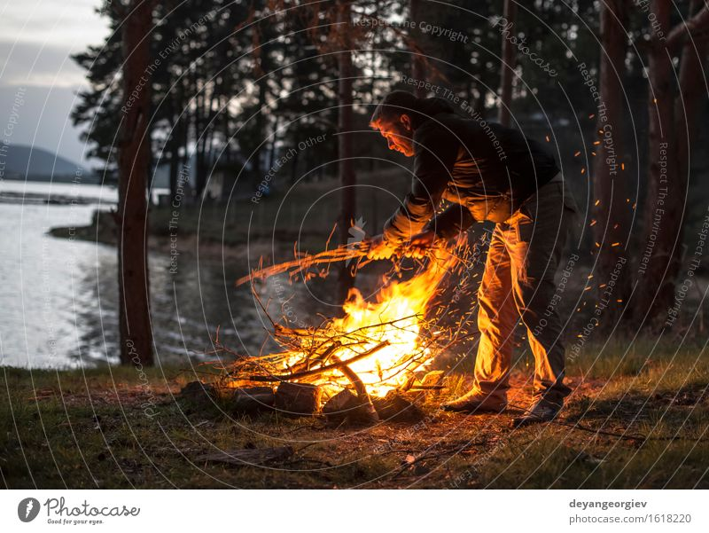 Man lights a fire in the fireplace in nature at night Human being Nature Vacation & Travel Summer Tree Forest Mountain Adults Warmth Natural Bright Tourism Wild