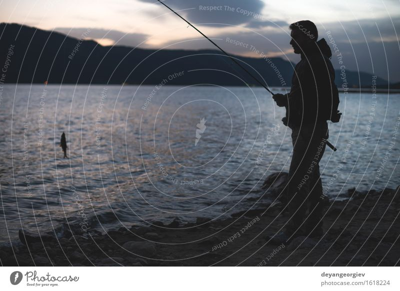 Man fishing on mountain lake Lifestyle Joy Relaxation Leisure and hobbies Vacation & Travel Mountain Sports Human being Adults Nature Lake River Dark casual