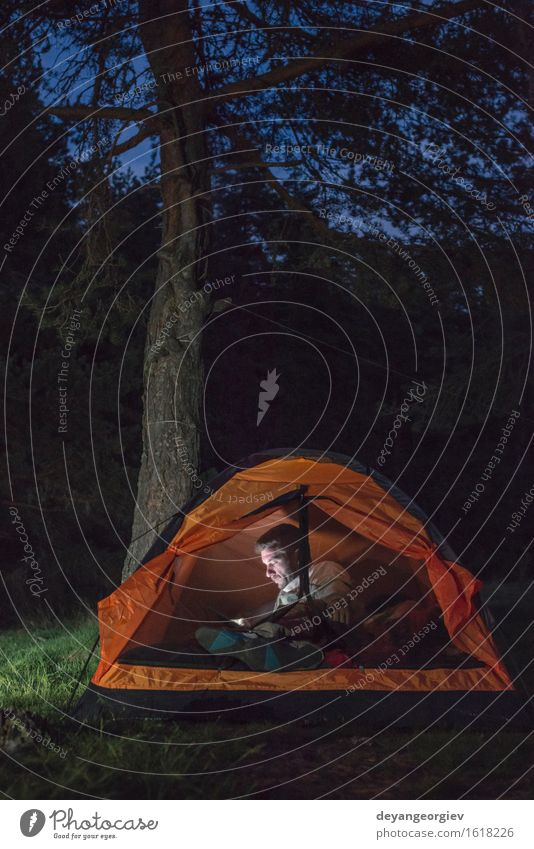 Man watching his smartphone in a tent Human being Vacation & Travel Summer Dark Forest Adults Lifestyle Happy Friendship Hiking Action Adventure Telephone