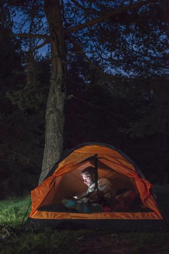 Man watching his smartphone in a tent Lifestyle Happy Vacation & Travel Adventure Camping Summer Hiking Telephone PDA Human being Adults Friendship Forest Dark