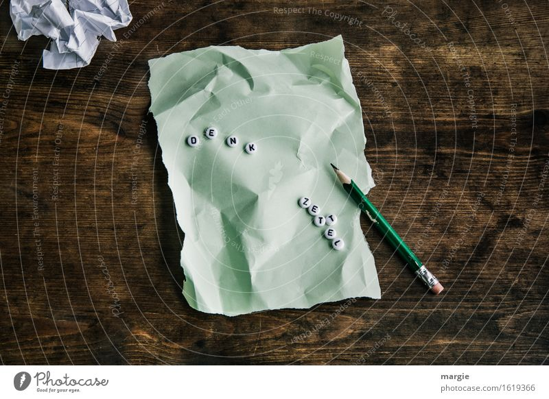 """The letters """"Denk Zettel"""" on a green crumpled sheet of paper and pencil on a wooden table Education School Study Professional training Office work Workplace"""