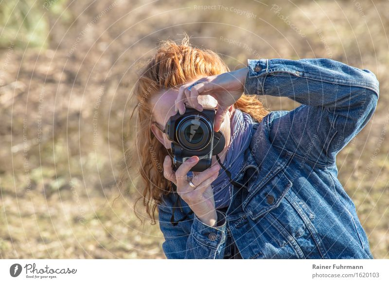 a woman quickly shoots some illegal photos Human being Feminine Woman Adults 1 Beautiful weather Red-haired Experience Communicate Surveillance Advertising