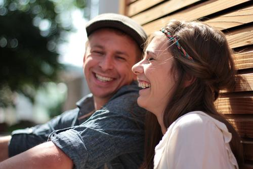 Man and woman laugh heartily while sitting leaning against a wall with rhombic strips Wedding Couple Partner Life 2 Human being 30 - 45 years Adults Sun Summer