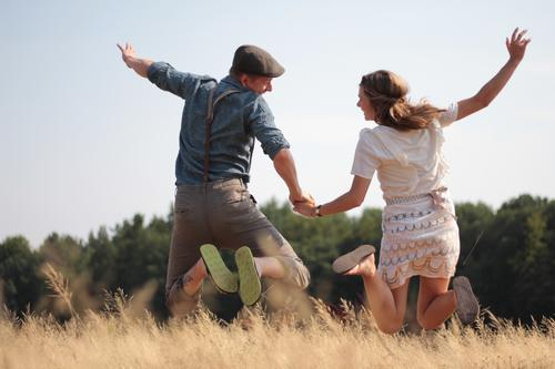 Human being Plant Summer Sun Joy Adults Warmth Life Couple Brown Together Jump Field Beginning Beautiful weather Dress