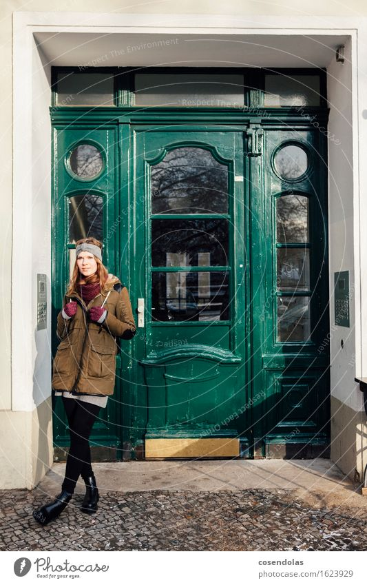Young woman standing in front of green front door Lifestyle Contentment Winter Human being Feminine Youth (Young adults) 1 18 - 30 years Adults Town