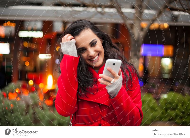 Beautiful Smiling Woman in red coat with mobile phone in hands, smartphone, urban scene woman smile smiling lifestyle girl person cold winter female technology