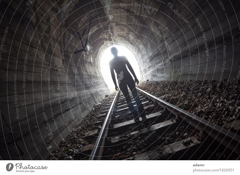Man in a tunnel looking towards the light adventure afterlife arched architecture asylum bright dark daylight escape enlightenment faith future hope
