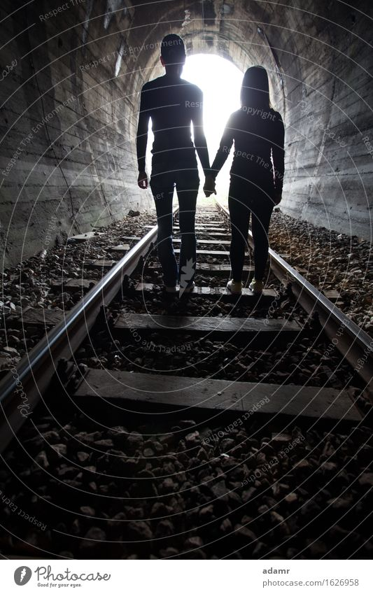 Couple walking together through a railway tunnel couple adventure arched asylum bright concept danger dark emigrants fugitive hidden holding hands hope