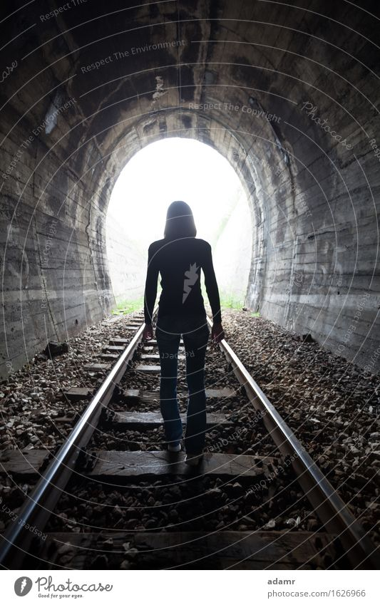 Women in a tunnel looking towards the light adventure afterlife arched architecture asylum bright dark daylight escape enlightenment faith future hope