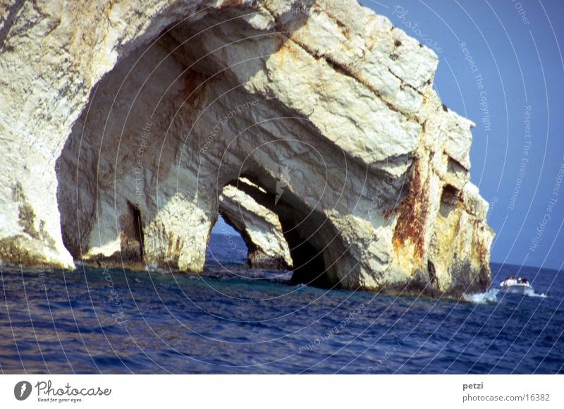 Caves in the Ionian Sea Ocean Water Cloudless sky Sun Summer Rock Waves Mediterranean sea Watercraft Blue Gray Vista Opposites: solid rock agitated water