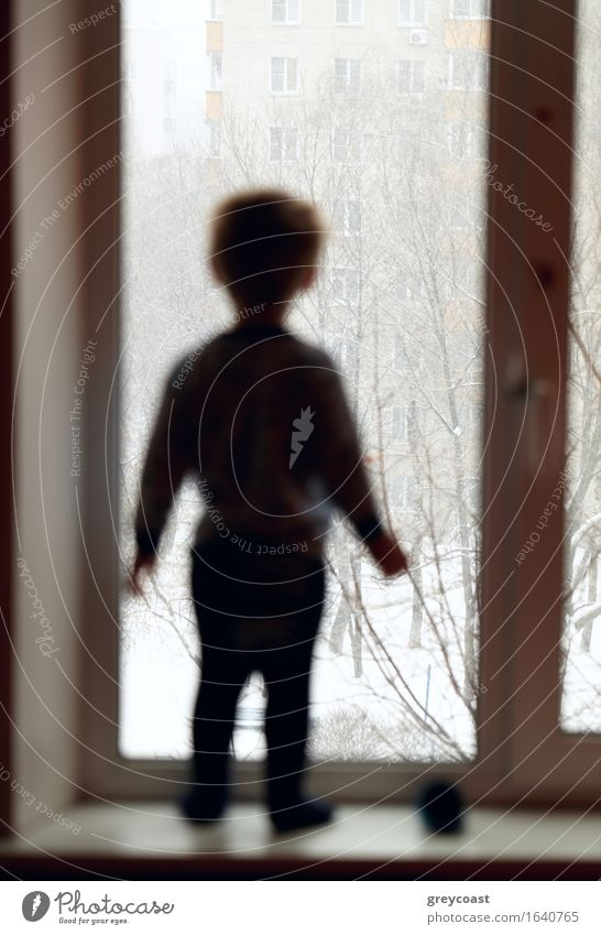 Boy is looking through the window. Human being Child White Loneliness Winter Sadness Boy (child) Small Think Dream Weather Meditative Body Infancy Stand