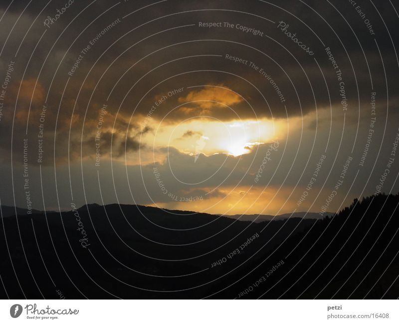 The day comes to an end Mountain Clouds Forest Yellow Gray Black Dusk sun hole Colour photo Exterior shot Copy Space top Copy Space bottom Silhouette Long shot