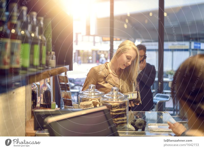 Attractive blond woman paying in a shop Shopping Happy Woman Adults Blonde Paying attractive Bank note bar Cafeteria Cashier Copy Space counter Customer