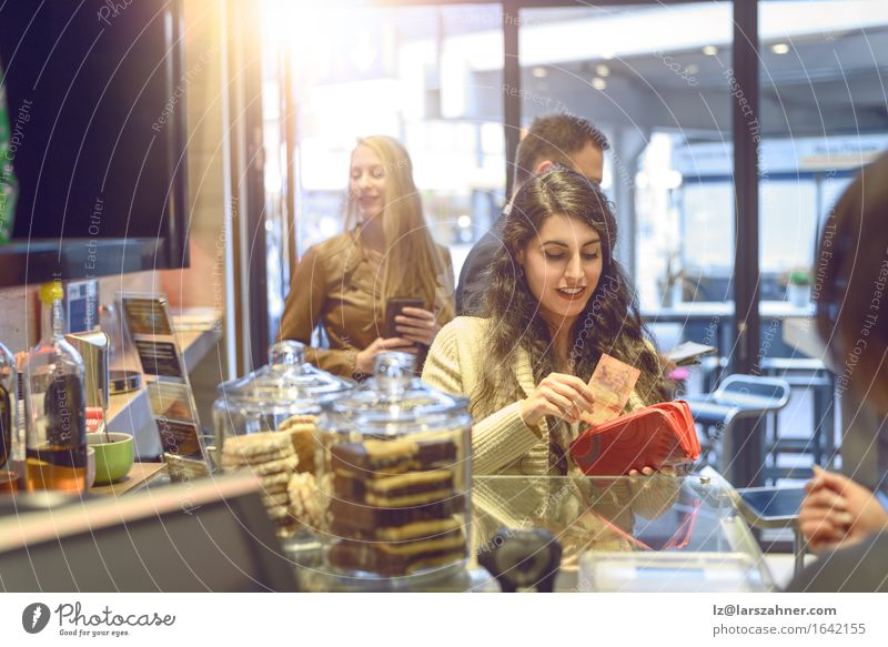 Attractive young woman paying in a shop Shopping Happy Woman Adults Paying attractive Bank note bar briunette Cafeteria Cashier Copy Space counter Customer