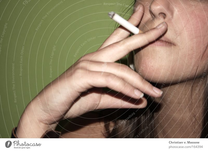 Young woman with a cigarette in front of a green background Colour photo Subdued colour Interior shot Close-up Copy Space left Copy Space top Neutral Background