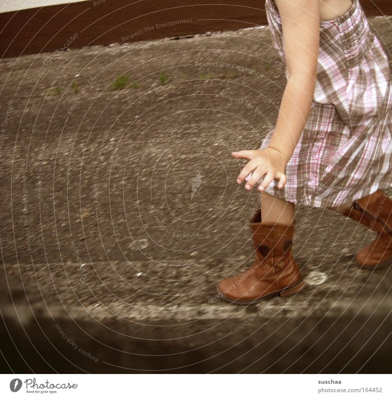 on the wall, on the ... Child Girl Wall (barrier) Summer Asphalt Dress Boots Pattern Contentment Highway ramp (entrance) Swing Movement Walking Human being