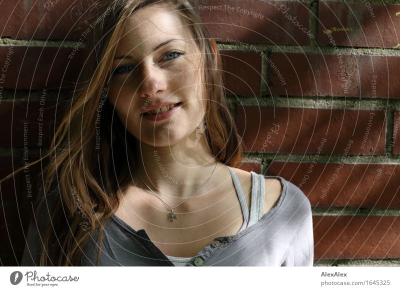 young woman stands in front of a brick wall and smiles - with light and shadow play Hair and hairstyles Face Wall (barrier) Young woman Youth (Young adults)
