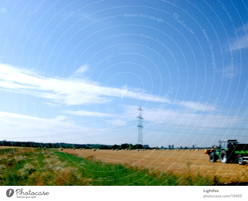Tractor flag Blur Field Bale of straw Autumn Electricity pylon Wheat Wheatfield Combine Electrical equipment Technology Landscape Dynamics Sky power lines