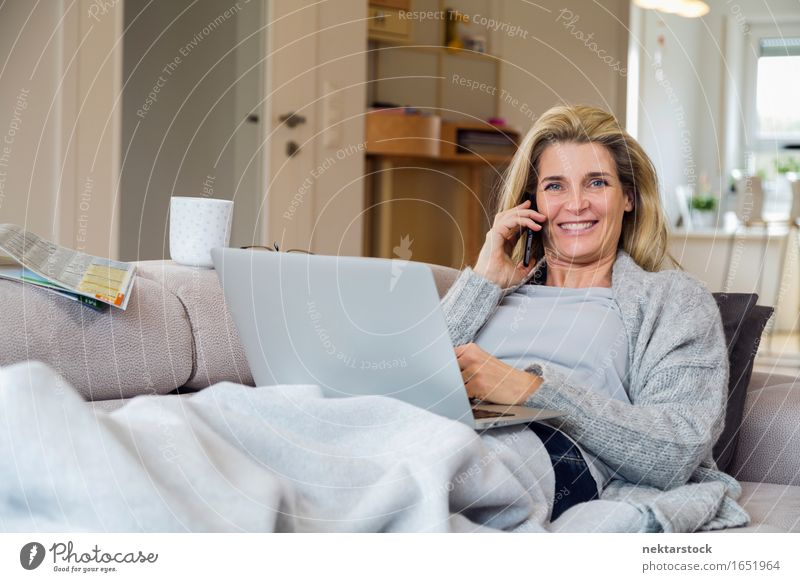 Blonde woman working from living room Lifestyle Happy Relaxation Leisure and hobbies Vacation & Travel Sofa To talk Telephone Computer Notebook Internet Woman